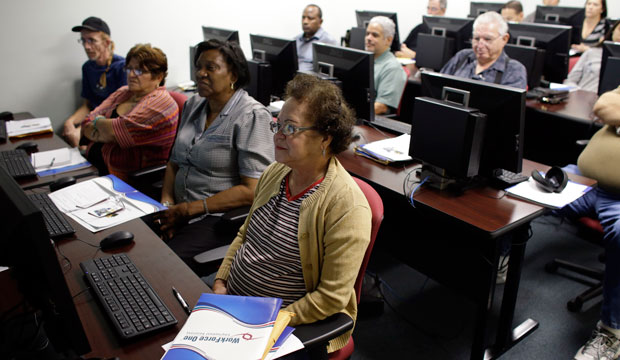 Margarita Sanchez, front, listens during a job-search workshop at WorkForce One in Davie, Florida.