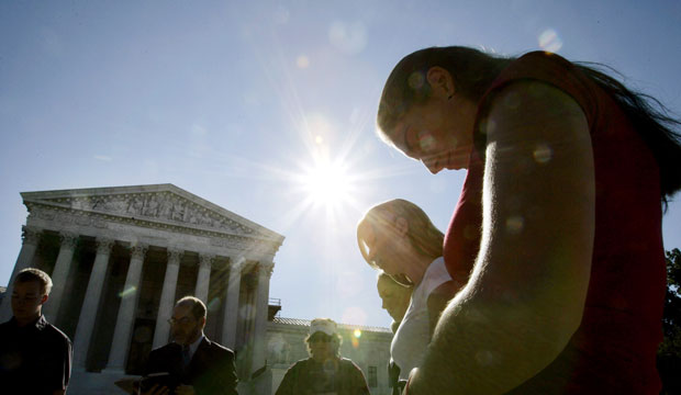 People pray in front of the Supreme Court.