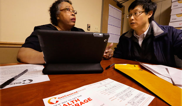 Navigator Mary Bennett, left, helps Min Lians, who is seeking help buying health insurance