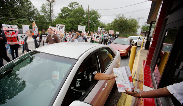 A worker hands a food order over to a customer as demonstrators march through a Burger King restaurant drive-thru