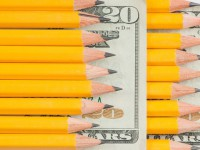 Pencils rest on a dollar bill