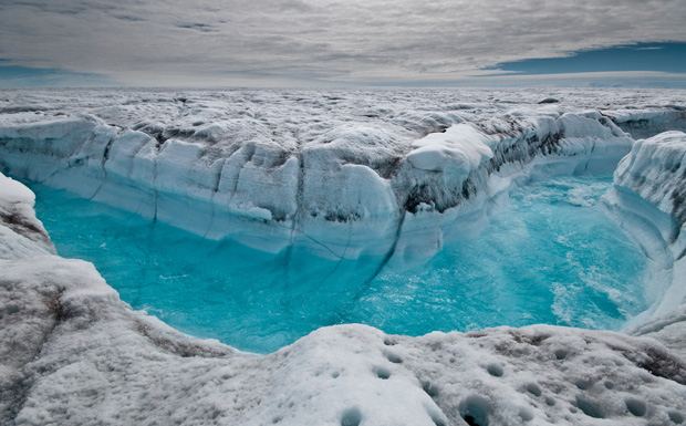 Melt water rushes along the surface of the Greenland Ice Sheet through a supraglacial stream channel, southwest of Ilulissat, Greenland.