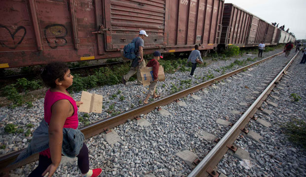 Migrants walk along the rail tracks after getting off a train during their journey toward the U.S.-Mexico border in Ixtepec, Mexico.