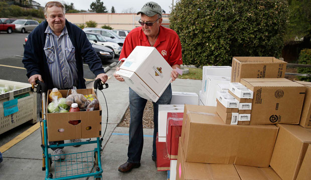 Steve Bosshard hands over a specially prepared box of food to Gordon Hanson at a food bank distribution in Petaluma, California, in January.