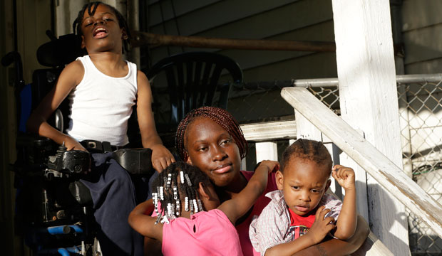 Patricia Jones is hugged by her 4-year-old daughter Pashalae Armstrong while outside her home in Newark, New Jersey, with her other children, Nature Harris and Latrell Armstrong.