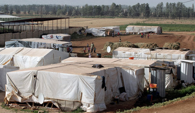 Syrian refugees walk outside their tents at a refugee camp in the eastern Lebanese town of Majdal Anjar, June 2014.