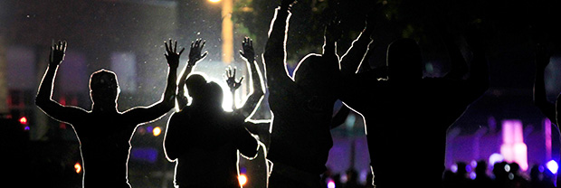 People raise their hands in the middle of the street as police wearing riot gear move toward their position in an attempt to get them to disperse, Monday, August 11, 2014, in Ferguson, Missouri.