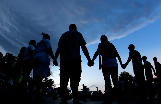 People stand in prayer after marching about a mile to the police station to protest the shooting of Michael Brown in Ferguson, Missouri.