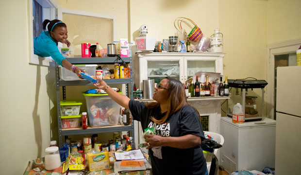 Jennifer Donald, whose family receives money from the Supplemental Nutrition Assistance Program, takes a box of taco seasoning from her daughter, October 2013.