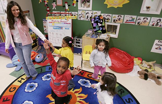 Three-year-old Nathan Austin, center, dances around his classroom with teacher Jennifer Grillo-Bates and classmates at the Egenolf Early Childhood Center in Elizabeth, New Jersey.