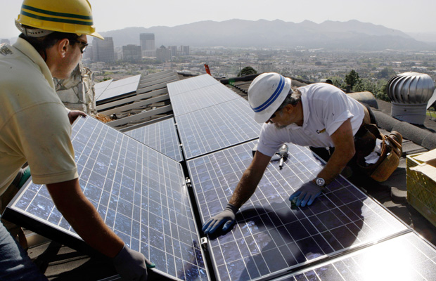 Edward Boghosian and Patrick Aziz, both employees of California Green Design, install solar electrical panels on the roof of a home in Glendale, California.