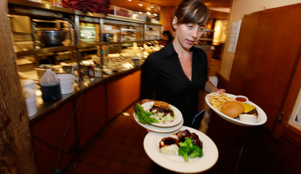 Wendy Harrison, a waitress at the Icon Grill in Seattle, carries food to a table as she works during lunchtime.