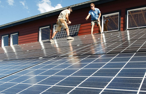 Workers install solar panels on the roof of a barn in Colorado.
