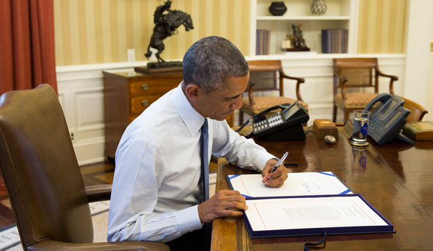 President Barack Obama signs H.J. Res 124, which includes appropriations to train and arm moderate Syrian rebels in the fight against ISIS, on September 19, 2014.