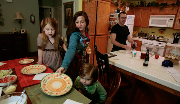 Cindy Reilly, center, sets the dinner table for her children Isabella, 7, left, Sierra, 4, and her husband Mike in the kitchen of their home in Nipomo, California.