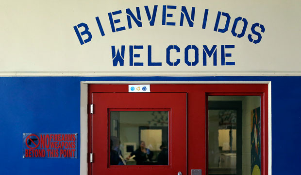 A Spanish and English welcome sign is seen above a door at the Karnes County Residential Center in Karnes City, Texas. The center has been retooled to house adults with children who have been apprehended at the border.