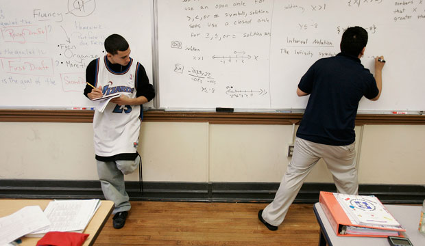 Jimmy Guevara, 17, left, stands next to the board taking notes during his 10th-grade math class as teacher Sammy Gutierrez works a problem at the Boston Community Leadership Academy pilot high school in the Brighton section of Boston, Massachusetts.