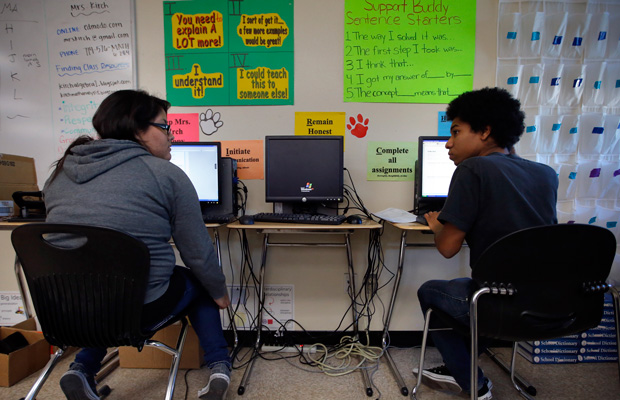 Eleventh grade students chat as they work on their homework in a pre-calculus class at Segerstrom High School in Santa Ana, California.