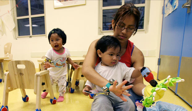 Jenny Gomez plays with her son Brandon Garcia, right, and Jocelyn Nava, left, at Edward A. Reynolds West Side High School's LYFE Center on August 7, 2007, in New York City.