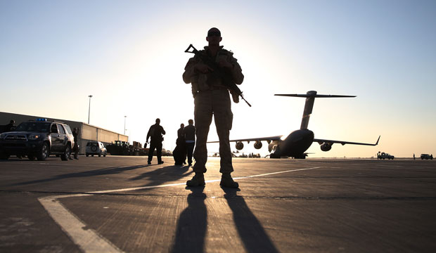 A soldier stands guard near a military aircraft in Kandahar, Afghanistan.