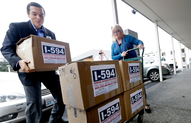 Supporters deliver boxes of petitions for Initiative 594 to the Secretary of State's office Wednesday, October 9, 2013, in Olympia, Washington.