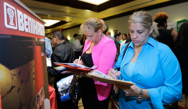 Job seekers Madelin Garcia, right, and Noharis Nunez fill out a job applications at a job fair in Miami Lakes, Florida.