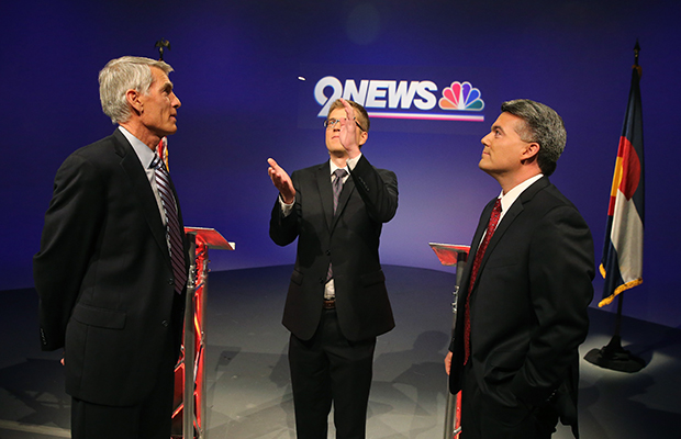 Incumbent Sen. Mark Udall (D-CO) and his opponent Rep. Cory Gardner (R-CO), right, watch a coin flip by moderator Brandon Rittiman to see who gets the first question during their final pre-election televised debate at 9News in Denver, October 15, 2014.