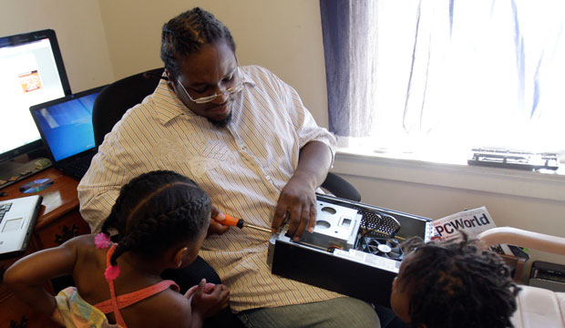 Carl Tabb, a 36-year-old father of 10 who hopes to earn a bachelor's degree in information technology from the University of Phoenix, takes apart a computer as his children watch.