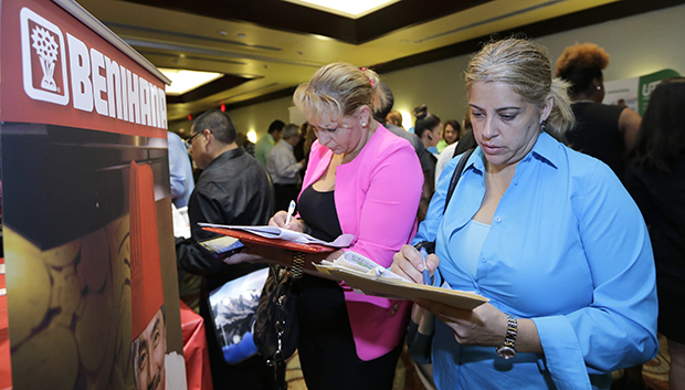 Job seekers Madelin Garcia, right, and Noharis Nunez fill out job applications at a job fair in Miami Lakes, Florida, October 22, 2014.