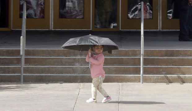 A young girl uses an umbrella for shade as she walks past the entrance of Sam Tasby Middle School in Dallas.