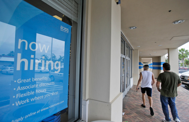 "Shoppers walk past a ""now hiring"" sign in North Miami Beach, Florida."