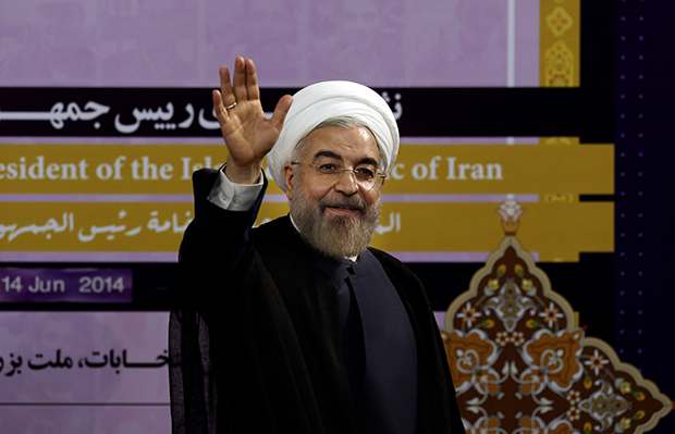Iranian President Hassan Rouhani waves after speaking at a press conference in Tehran, Iran, June 14, 2014.