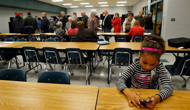 Destiny Davis plays a game on a cell phone as she waits for her mother to vote at Slater-Marietta Elementary School on Election Day, November 2012.
