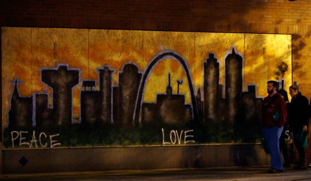 People walk by a mural on a boarded-up business on November 25, 2014, in south St. Louis, Missouri.