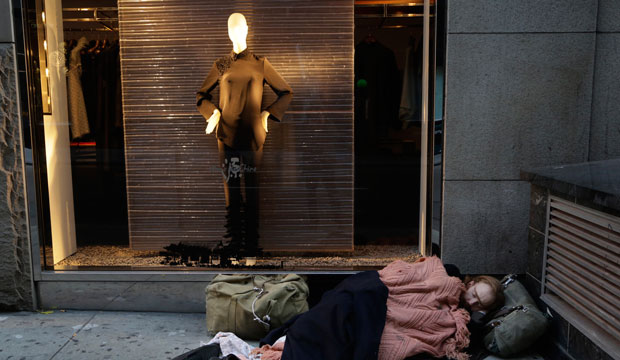 A homeless man sleeps on the sidewalk under a holiday window at Blanc de Chine in New York.