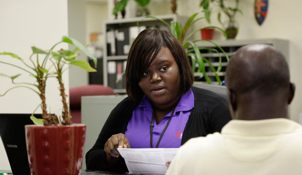 Navigator Samantha Joseph assists a client in signing up for health insurance under the Affordable Care Act at Sant La, a center in Miami's Little Haiti neighborhood.