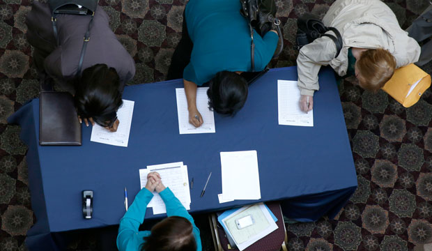 Job seekers sign in before meeting prospective employers during a career fair at a hotel in Dallas, January 2014.