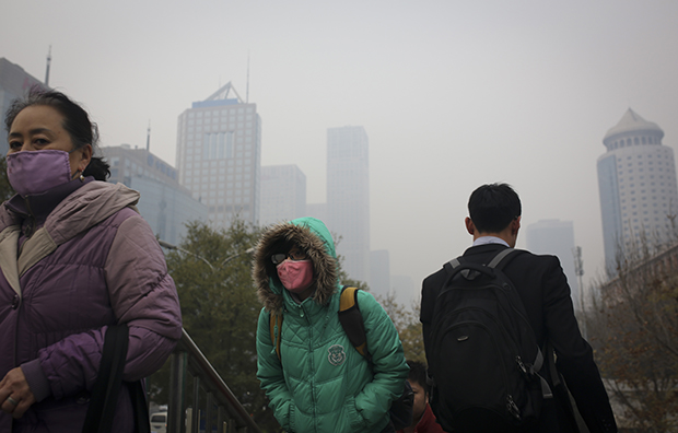 People wearing masks to protect themselves from pollutants walk on a pedestrian overhead bridge as city skylines are shrouded with haze in Beijing, China, Wednesday, November 19, 2014.
