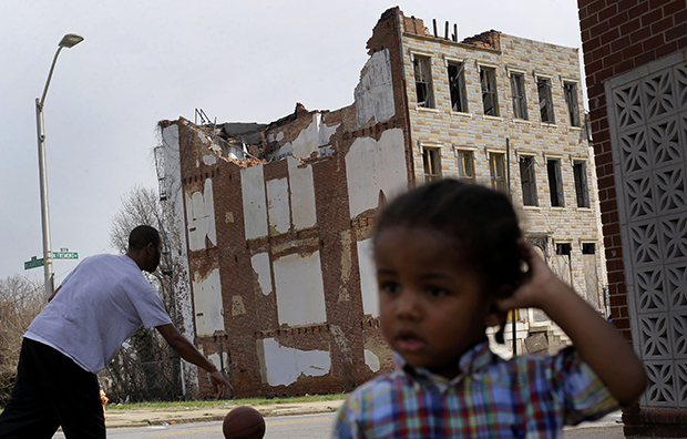 A boy whose family asked that he not be identified plays across the street from a partially collapsed row house in Baltimore, Maryland, April 8, 2013.