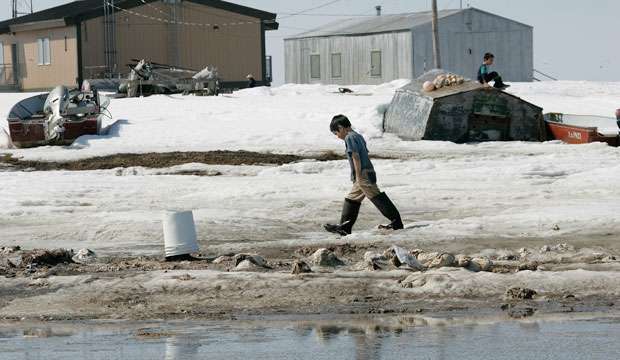 A boy walks along the banks of the Newtok River in the village of Newtok, Alaska.