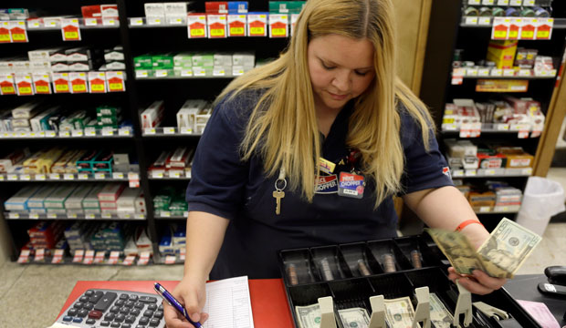 Amy Jennewein reconciles a cash register drawer during her shift at a grocery store in House Springs, Missouri.