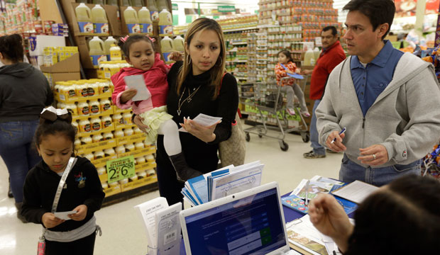 Grocery shoppers stop at a Blue Cross Blue Shield kiosk promoting the Affordable Care Act at Compare Foods in Winston-Salem, North Carolina.