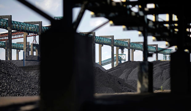 Piles of coal sit below conveyor belts at the Dominion Terminal Associates coal terminal, front, and Kinder Morgan coal terminal, back, in Newport News, Virginia.