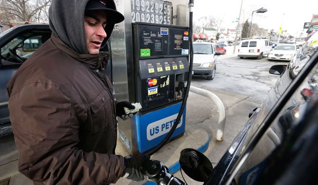 Justin Zahreddine, of Quincy, Massachusetts, fuels up at a gas station where regular unleaded was listed for a cash price of $1.99 per gallon, Jan. 7, 2015, in Boston.