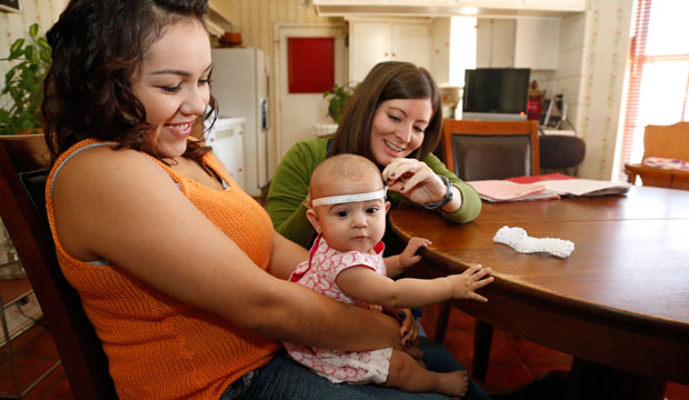 Sara Young, right, measures Sophia Payne, center, held by her mother, Cristina Swank, during a home visit in Oklahoma City.