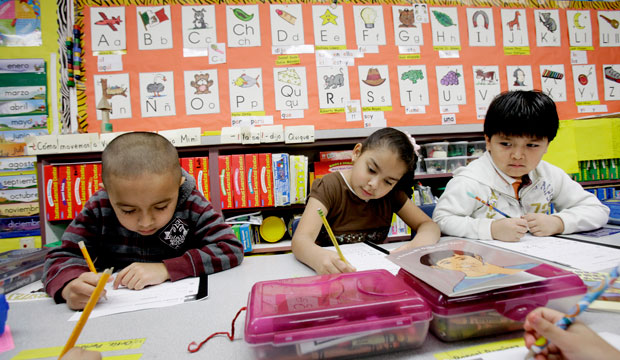 Five-year-old kindergarden students Gael Alvarado, left, Perla Ortiz, center, and Yahir Perez do school work in a bilingual English-Spanish class at Hanby Elementary School in Mesquite, Texas, in 2011.