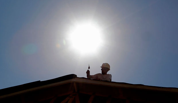 A roofer works under the midday sun in Gilbert, Arizona, in July 2014.