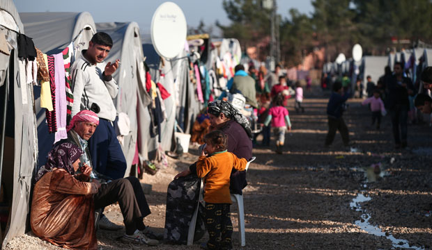Syrian refugees who fled violence in Kobani are seen outside their tents in a camp in Suruc, Turkey.