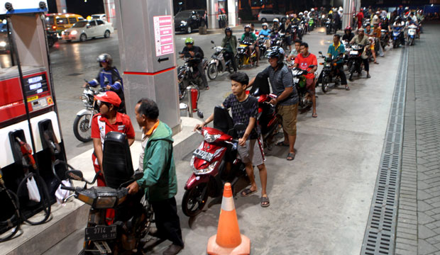 Motorists in Indonesia line up at a gas station before the fuel-price hike takes effect in June 2013.