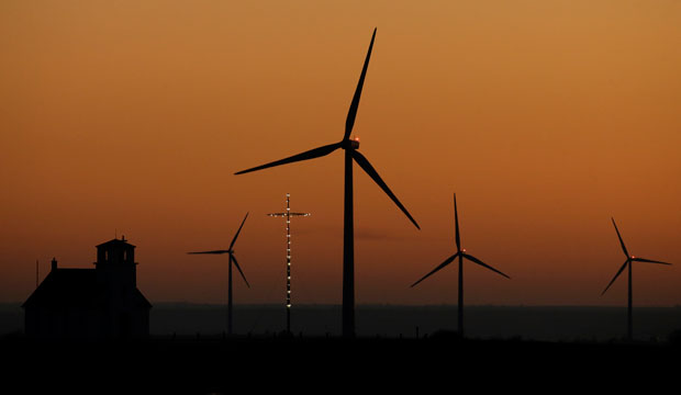 Wind turbines from the Smoky Hills Wind Farm dwarf the Excelsior Lutheran Church at dusk on Friday, December 5, 2014, near Wilson, Kansas.